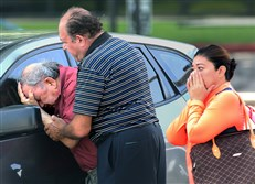 A man is comforted Tuesday after finding out that a relative drowned in her truck in Houston. Storms during the holiday weekend dumped record rainfall on Texas, causing major flooding throughout the state, and spawned tornadoes.