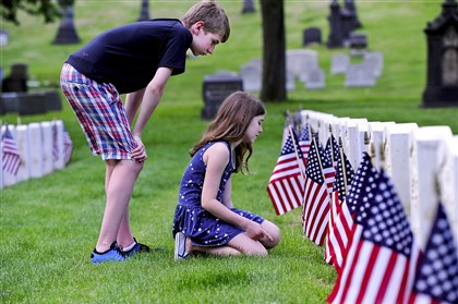 "Ike Goldman and his sister, Maggie Goldman, from Mt. Lebanon, visit the graves of veterans at Allegheny Cemetery in Lawrenceville. Their mother, Katie Goldman, said ""we didn't want the day to go by without thinking about the veterans."""