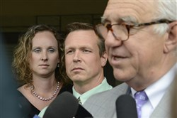 Drew Zoldak, suspended as a teacher at Plum Senior High School, center, listens as his attorney, Alexander H. Lindsay Jr., right, speaks to the media following Mr. Zoldak's preliminary hearing this morning in Plum. At left is Mr. Zoldak's wife. He was held for trial on two counts of intimidating a victim in a sexual assault involving another teacher at the high school.