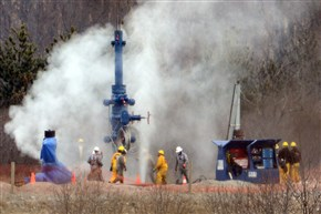 Gas vents skyward as Chevron contractors maneuver a new well cap in place on one of the leaking gas wells that blew up in 2014, killing one worker and injuring another.