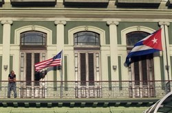 A man stands near the national flags of the U.S. and Cuba on the balcony of a hotel in Havana being used by the first U.S. congressional delegation to Cuba since the change of policy announced by President Barack Obama on Dec. 17.