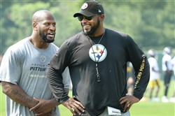 Steelers head coach Mile Tomlin jokes with James Harrison during an OTA session last month at the team's training facility on the South Side