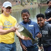 At Camp Kon-O-Kwee, Beaver County, Kameron Johnson of the seventh grade class at Woodland Hills Junior High School landed a 4-pound largemouth bass. He got a little help from Woodland Hills' Mike Jones.(right) and Michael Dofner (left), a Creek Connections volunteer and Robert Morris University student. The fishing event was organized by the state Fish and Boat Commission as part of Allegheny College's Pittsburgh Area Research Symposium.