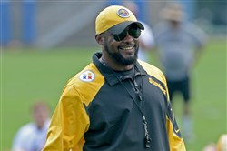 Steelers head coach Mike Tomlin talks with players as they stretch during minicamp on the South Side in June.