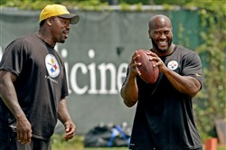 Steelers outside linebackers coach Joey Porter talks with James Harrison during minicamp last month at the team's facility on the South Side.
