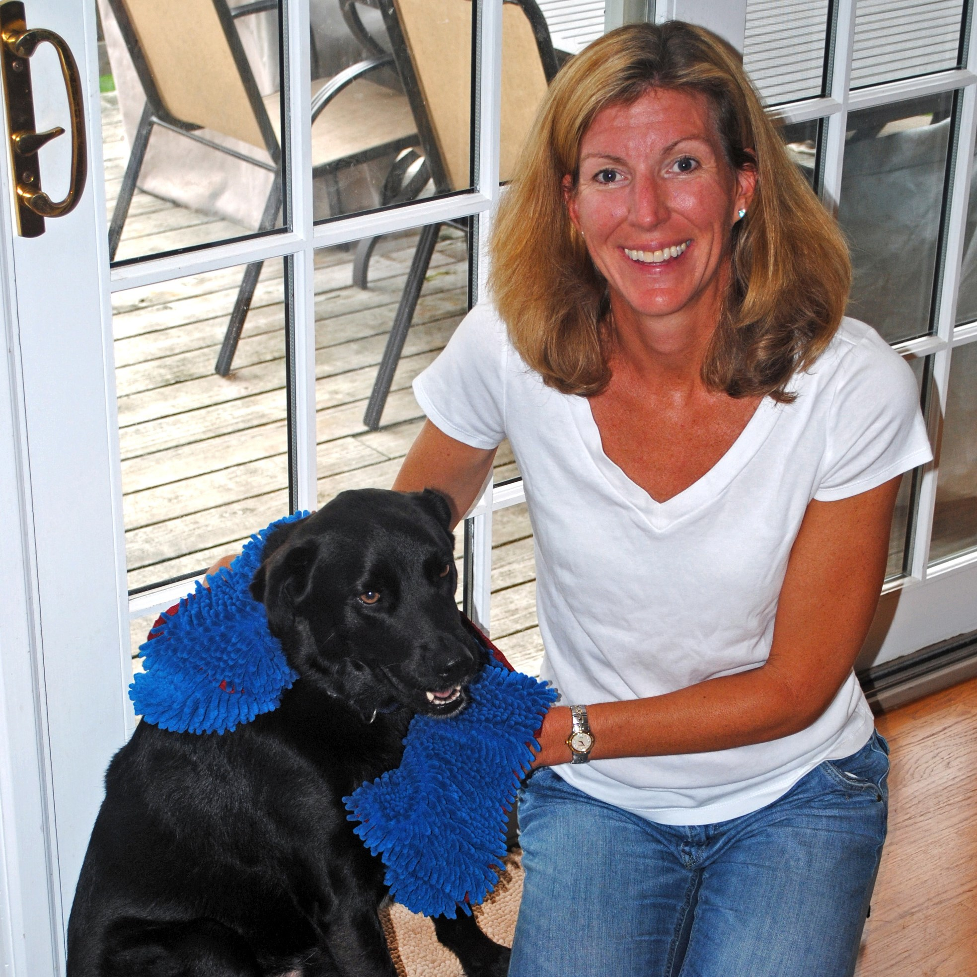 "In this undated photo provided by Soggy Doggy Productions LLC, Joanna Rein, of Larchmont, N.Y., poses at her home with her Labrador-collie named Buddy. Because Buddy was always tracking mud or water into the house, Rein created ""Soggy Doggy,"" a doormat that absorbs most of the mess on the mutt. Rein has sold more than 300,000 mats online since 2010. (Richard A. Randall/Soggy Doggy Productions LLC via AP)"