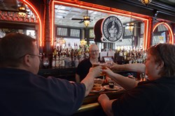 Glenn Miller, left to right, his sister Stacy Miller and Alison Kaelin, all of Observatory Hill, toast with beers as bartender Patrick Madden watches at Max's Allegheny Tavern on the North Side.