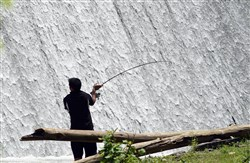A fisherman casts his fishing line at the base of the spillway at Canonsburg Lake.