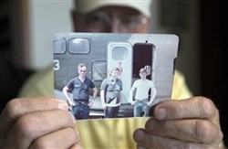 Retired Air Force Reserve Tech Sgt. Ed Kienle, 73, holds a picture of himself, left, and fellow reservists June 11 in Wilmington, Ohio. The Department of Veterans Affairs has been working to finalize a rule that could cover more than 2,000 military personnel, including Sgt. Kienle, who flew or worked on Fairchild C-123 aircraft in the U.S. from 1972 to 1982.