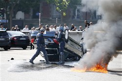 French riot police stand next to an overturned car Thursday as striking French taxi drivers demonstrate at the Porte Maillot to block the traffic on the Paris ring road during a national protest against car-sharing service Uber in Paris.