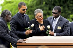 Sharon Risher puts her hand to her heart Thursday while standing over the casket of her mother, Ethel Vance, who was later buried at the Emanuel AME Church cemetery in Charleston, S.C. Ms. Vance was one of the nine people killed during a shooting attack at the church.
