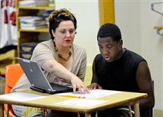 Allen Carter, 14, gets help from his English teacher, Wendy Koval, at the Rankin Promise program in Rankin.