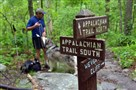 Illustrator Walter Cumming and his Malamute Tanook take a break near the sign posts at Weverton Cliffs along the Appalachian Trail near Harpers Ferry, W.Va.