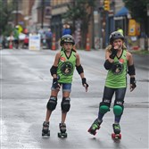 Ashley Smith and Sophia Swinderski roller skating down Butler Street in Lawrenceville on Sunday during OpenStreetsPGH, a free public event that make streets pedestrian-only.