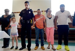 Officer Souroth Chatterji joins community members in prayer before the start of a weekly gathering at Kingdom Life Fellowship in Knoxville in which Pittsburgh police officers volunteered to serve meals.