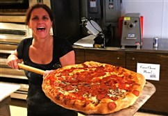 Shelly Farren, proprietor of Shelly Pie Pizza in Turtle Creek, presents a pepperoni and mushroom pizza just our of the oven.