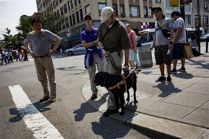 150701_Tim Hornik_Jika Gonzalez_120-13 Veteran Tim Hornik, 35, is shown with his guide dog, Black Jack. The streets in Flushing, Queens, are busy and crowded. It can be a challenge to cross streets and maneuver through crowds.