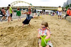 Olivia Anderson, 4, plays in the sand as her brother Elliott Anderson, 5, does cartwheels at the Travel to the Beach Kids Korner of the EQT Three Rivers Regatta in Point State Park on Friday.