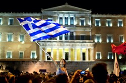 "A supporter of the ""No"" vote waves a Greek flag in front of the parliament Sunday after the results of the referendum at Syntagma square in Athens, Greece."