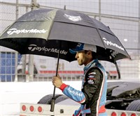 Driver Aric Almirola walks to pit road during a rain delay at a NASCAR race Sunday at Daytona International Speedway in Daytona Beach, Fla.