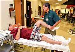 John Meeker, 51, of Nottingham, has his knee worked on by physical therapist Mike Degregorio at Allegheny Health Network Outpatient Care Center in McMurray.  Mr. Meeker had a total knee replacement and was discharged the same day as his surgery.