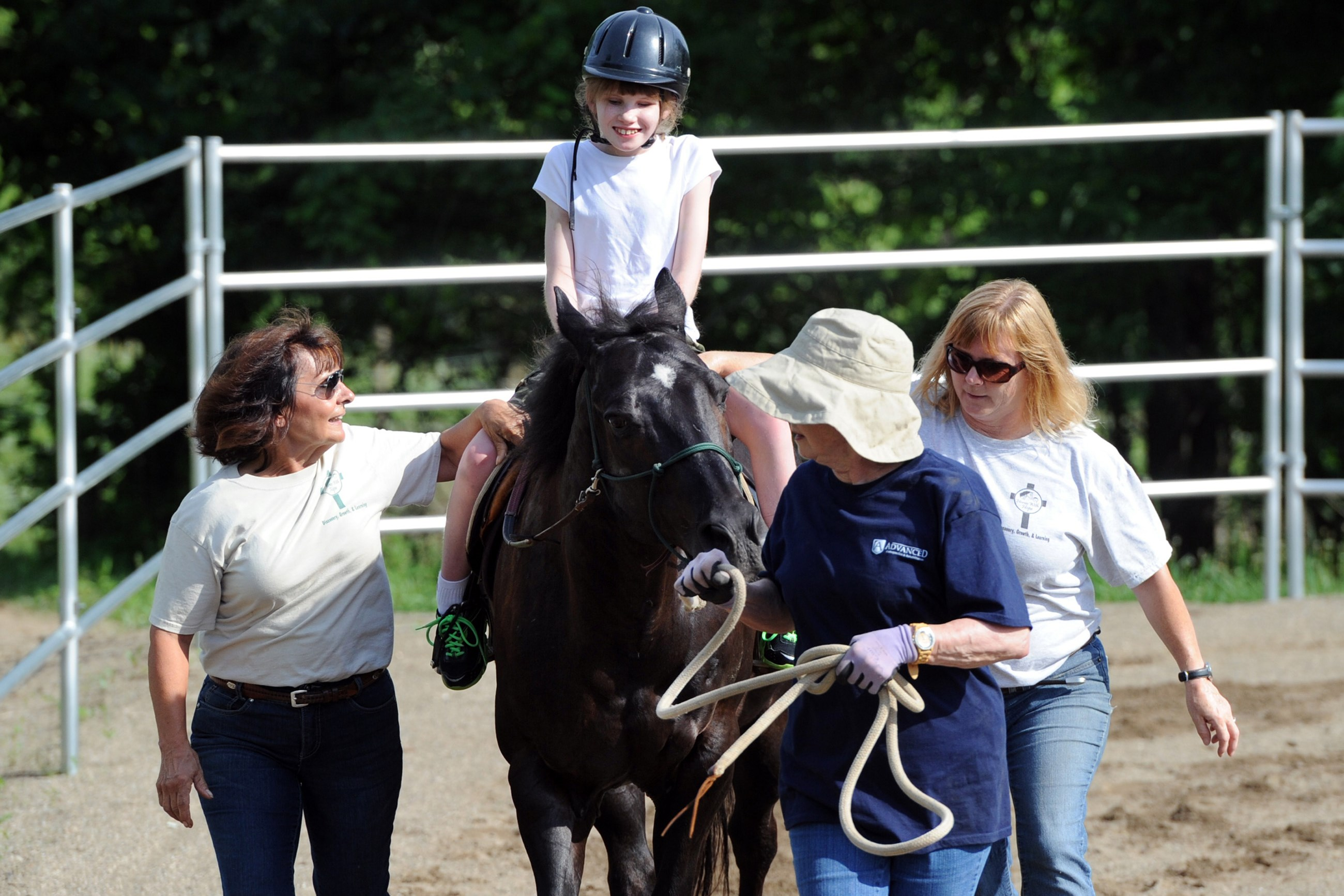 Kaylee Doyle, 12, of Scott rides at the Horses with Hope ranch in Bethel Park. Volunteers Joanne Murdy, left, Barbara Bach, center, and Anne Davis assist Kaylee around the track.