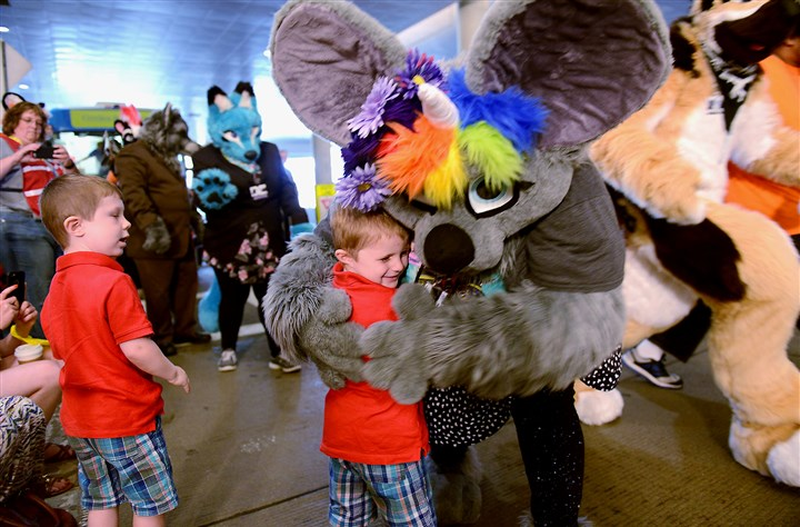 20150711ppFurries3LOCAL-2 Thomas Raupp, 4, from Upper St. Clair gets a surprise hug from a furry during the Fursuit Walk along the 10th Street underpass of the David L. Lawrence Convention Center during the Anthrocon convention Saturday. His brother Louis, 4 watches.