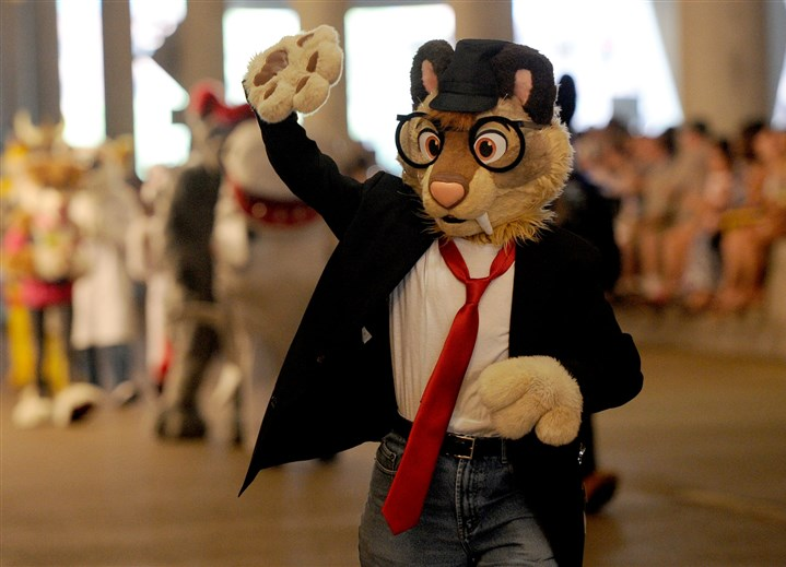 20150711ppFurries1LOCAL A Furry waves to the crowd during the Fursuit Walk along the 10th Street underpass of the David L. Lawrence Convention Center during the Anthrocon convention Saturday, July 11, 2015. His brother Louis, 4 watches.