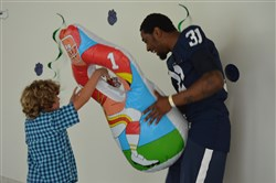 Freshman Daiquan Kelly took turns holding up an inflatable target while chasing after kids during the team's visit to Hershey Children's Hospital on July 15, 2016.
