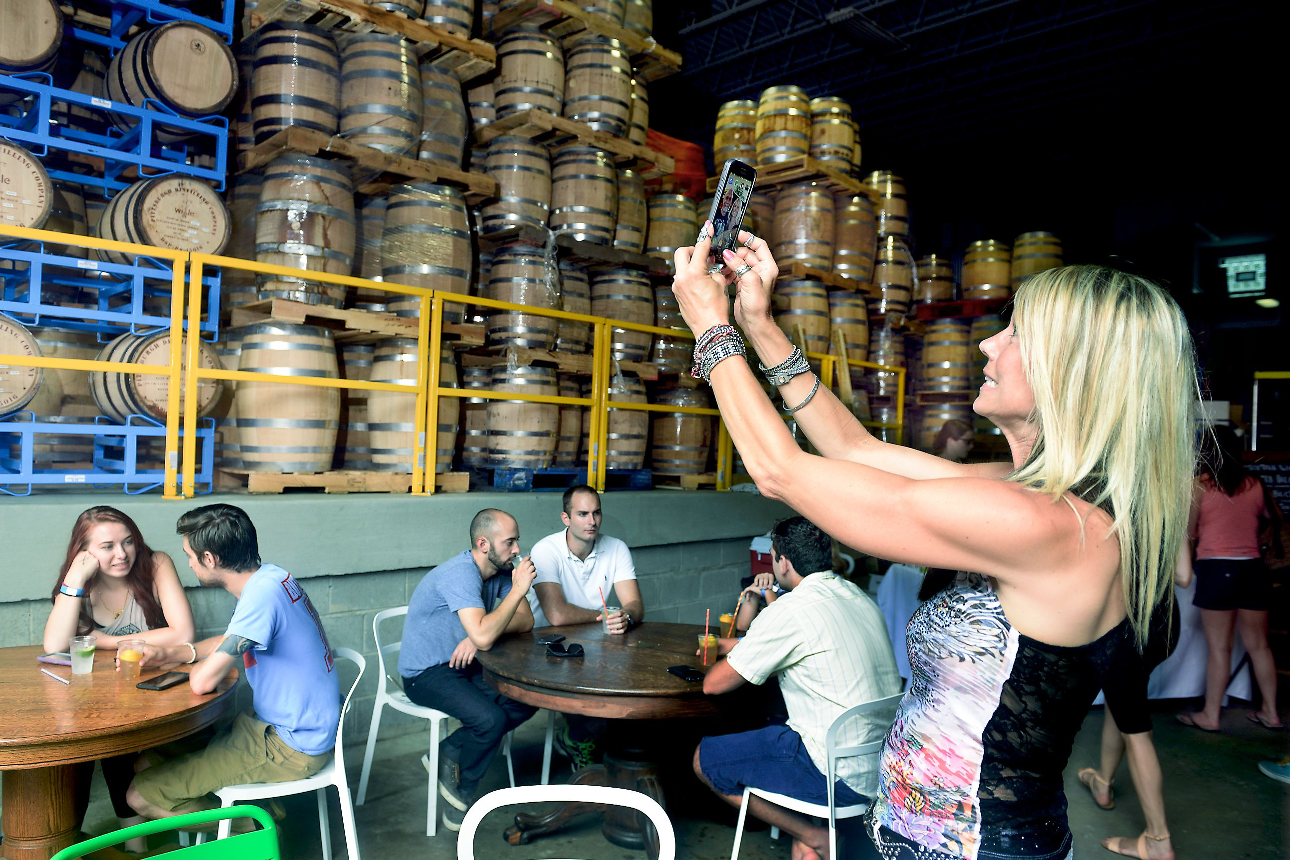20150711bwWigleDistinction01x Paige Conklin of Ellwood City takes photos of barrels at Wigle Whiskey Barrelhouse on the North Side earlier this summer.