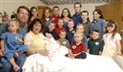 "In this Aug. 2, 2007 file photo, Michelle Duggar, left, is surrounded by her children and husband Jim Bob, second from left, after the birth of her 17th child in Rogers, Ark. TLC is officially cancelling ""19 Kids and Counting."" The hit reality show ""will no longer appear on the air,"" the network told The Associated Press on Thursday."