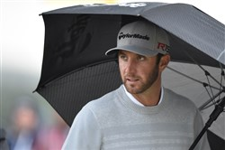 Dustin Johnson leaves the 10th tee under an umbrella Friday as rain picks back up in the second round of the British Open in St. Andrews, Scotland.