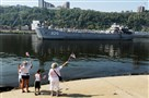 People wave flags for the LST 325 as it heads toward the North Shore during its last visit to Pittsburgh in 2010.