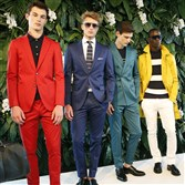 Models pose in multi-colored suits and a casual jacket with sweater ensemble during the Tommy Hilfiger presentation at Men's Fashion Week in New York.