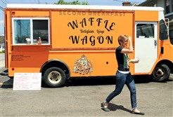 A Second Breakfast Waffle Wagon customer walks into Coffee Buddha to eat after receiving her order from the food truck. The Waffle Wagon serves customers every Thursday in the parking lot of the Ross coffee shop.