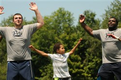 Trystin Ingram, 9, from Homewood, works out with Pitt's Tony Pilato and Calvin Hamilton at a football clinic Friday at the Mel Blount Youth Home in Claysville.