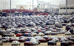 New cars parked outside the Mitsubishi Motors plant in Normal, Ill.