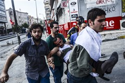 Protesters carry a wounded man Saturday in Istanbul, Saturday during clashes between police and protesters denouncing the deaths of 32 people at an suicide bombing Monday in Suruc, southeastern Turkey.