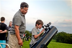 Dan Peden of Brookline, left, with Philip Sahady, 7, of Republic, Fayette County, using Mr. Peden's 8-inch refractor telescope at the Amateur Astronomers Association of Pittsburgh's Star Party at Mingo Observatory in Mingo Creek County Park in Washington County