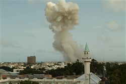Smoke rises from the Jazeera hotel during an attack in Somalia's capital Mogadishu today. At least 13 people were killed when Somalia's al Shabaab Islamist militant group drove a car packed with explosives at the gate of a hotel, police and the rebel group said.