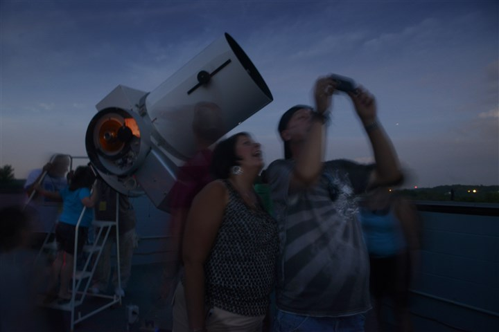 20150724bwStarsMag02-2 Karen McCurry of Whitehall, left, and her brother Darin McCurry of Lawrenceville take pictures at the Amateur Astronomers Association of Pittsburgh's Star Party at Mingo Observatory in Mingo Creek County Park in Washington County. In the background is the park's 24-inch Ritchey-Chretien Reflector telescope.