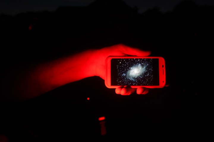 20150724bwStarsMag03x-4 Fred Klein of Monroeville shows his photo stored on a cell phone that he took with his 11-inch reflector mirror telescope of Galaxy M-33. The red light helps you keep your night vision.