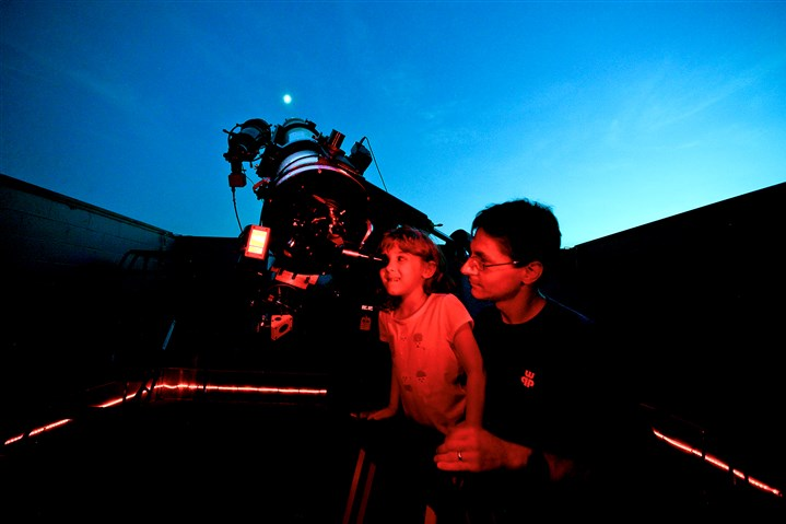 20150724bwStarsMag01x-1 Amber, 5, and her dad Mike Mistick of North Strabane, get a look at the moon at the Amateur Astronomers Association of Pittsburgh's Star Party at Mingo Observatory in Mingo Creek County Park in Washington County. They are viewing with a 10-inch refractor telescope, with the red used to help them keep their night vision.