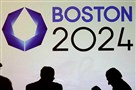 Shadows of organizers and reporters pass a video display screen prior to a news conference by organizers of Boston's campaign for the 2024 Summer Olympics in January.