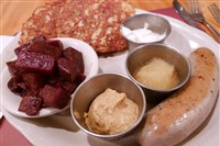 A weisswurst served with mustard, potato pancakes (with sour cream and applesauce) and roasted beets.