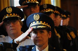 Commander Linda Rosato- Barone, center, stands with officers waiting to be promoted. Karen Dixon, left, was promoted to commander, along with two officers to lieutenant and five to sergeant.