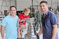 Former Chicago Blackhawks player and Pittsburgh native Brandon Saad poses for photograph with Chief Master Sergeant Richard Lundy and two-year-old Blake Lundy. The Cup was on display yesterday for military members and their families.