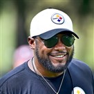 Steelers head coach Mike Tomlin jokes with players prior to workouts Wednesday at St. Vincent College in Latrobe.