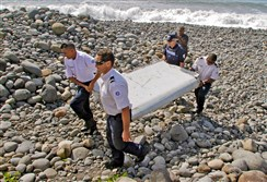 French police officers carry a piece of debris from a plane in Saint-Andre, Reunion Island on July 29. French investigators confirmed today that the flaperon was part of the Boeing 777 of Malaysia Airlines Flight 370 that went missing last year with 239 people aboard.