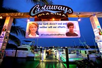 A banner hangs Friday at the Castaways Marina with pictures of Austin Stephanos and Perry Cohen.